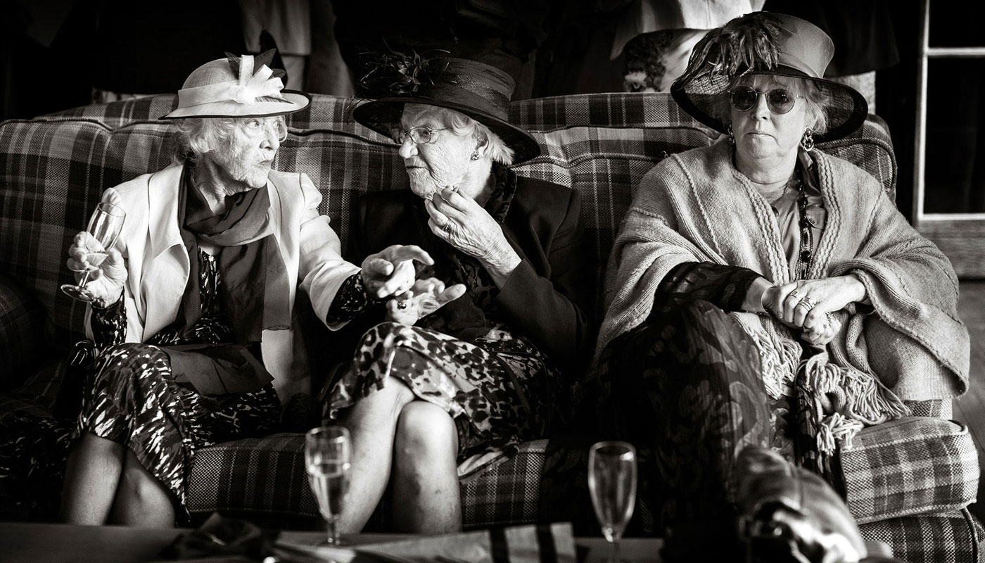 three old ladies at a wedding sitting talking