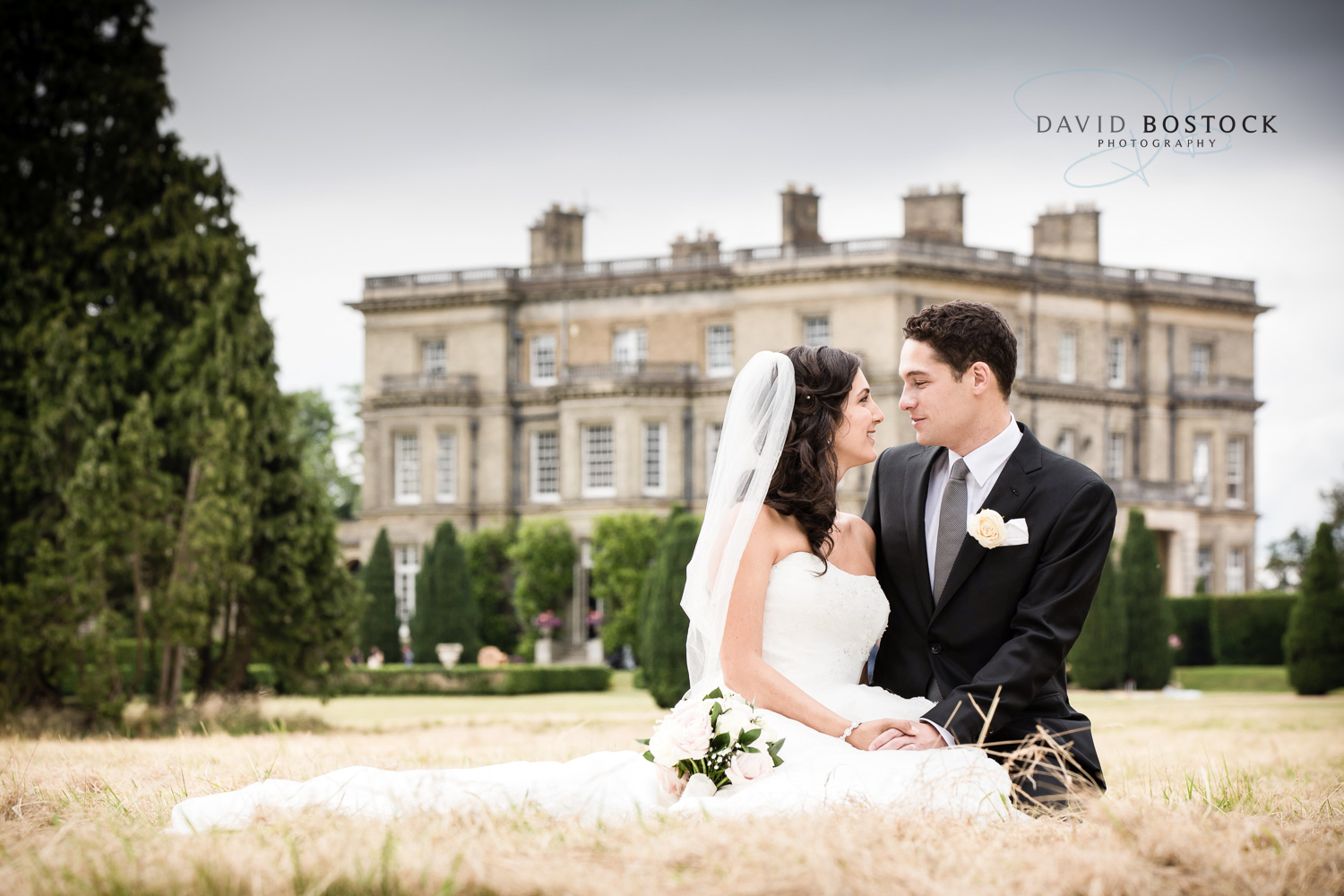 bride and groom sitting on the grass in front of hedsor house
