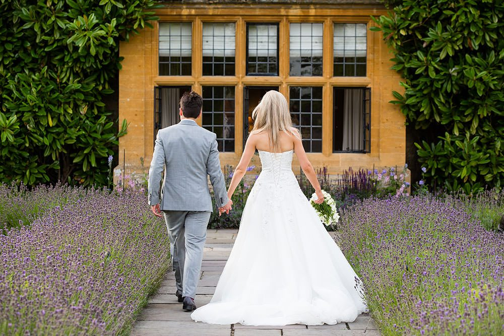 bride and groom walking away hand in hand at Le Manoir aux Quat'Saisons