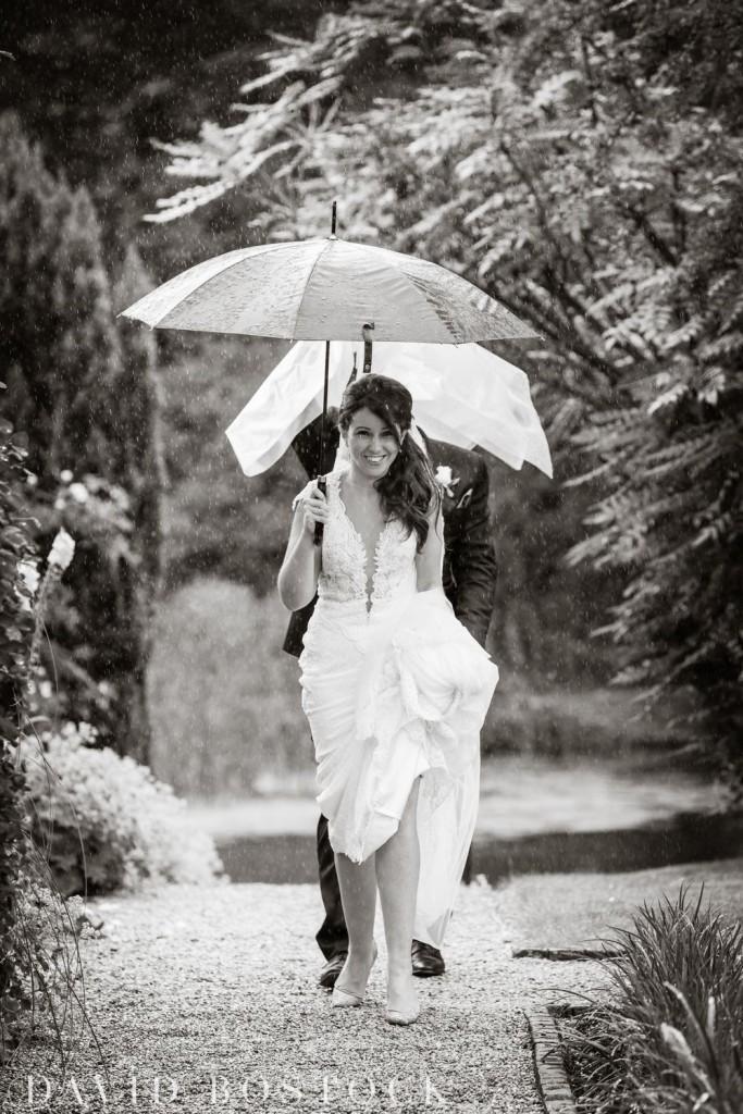 bride walking in the rain at le manoir wedding