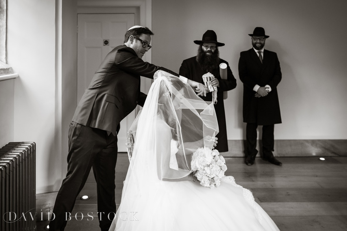 groom puts veil in place
