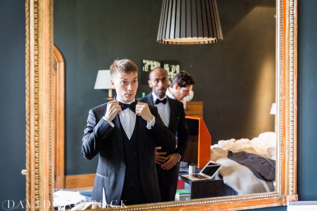 Eynsham Hall Wedding groom tieing bow tie