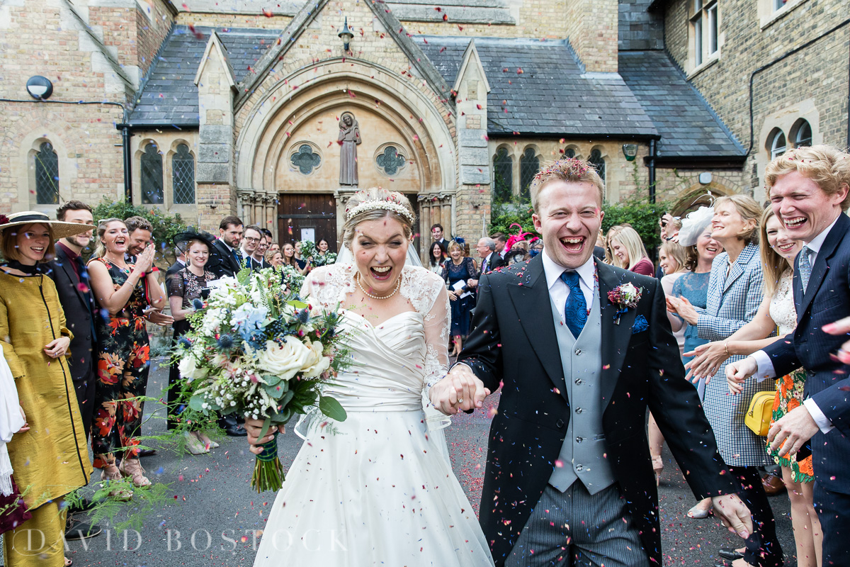 bride and groom walking through hail of confetti
