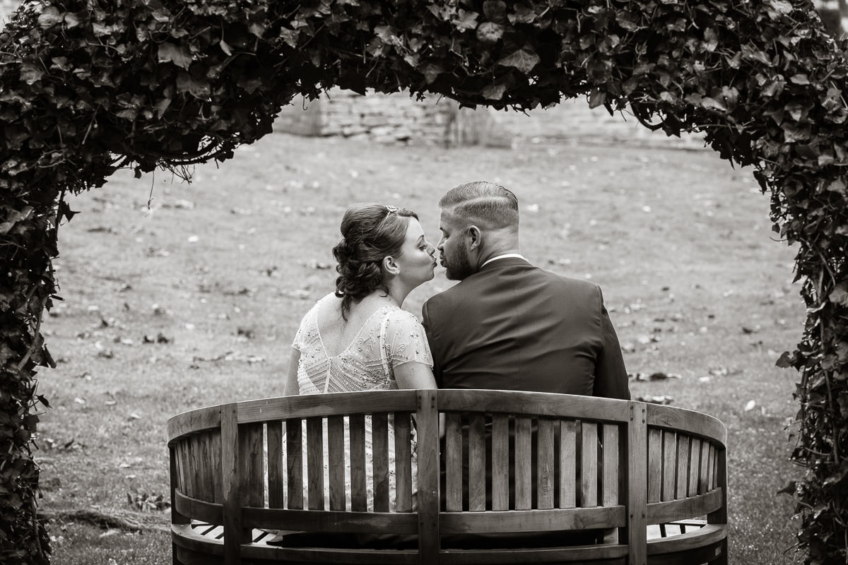 Cripps Barn wedding bride and groom kissing on bench