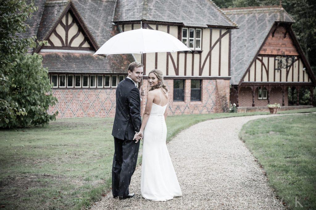 The Dairy Waddesdon wedding bride and groom under umbrella