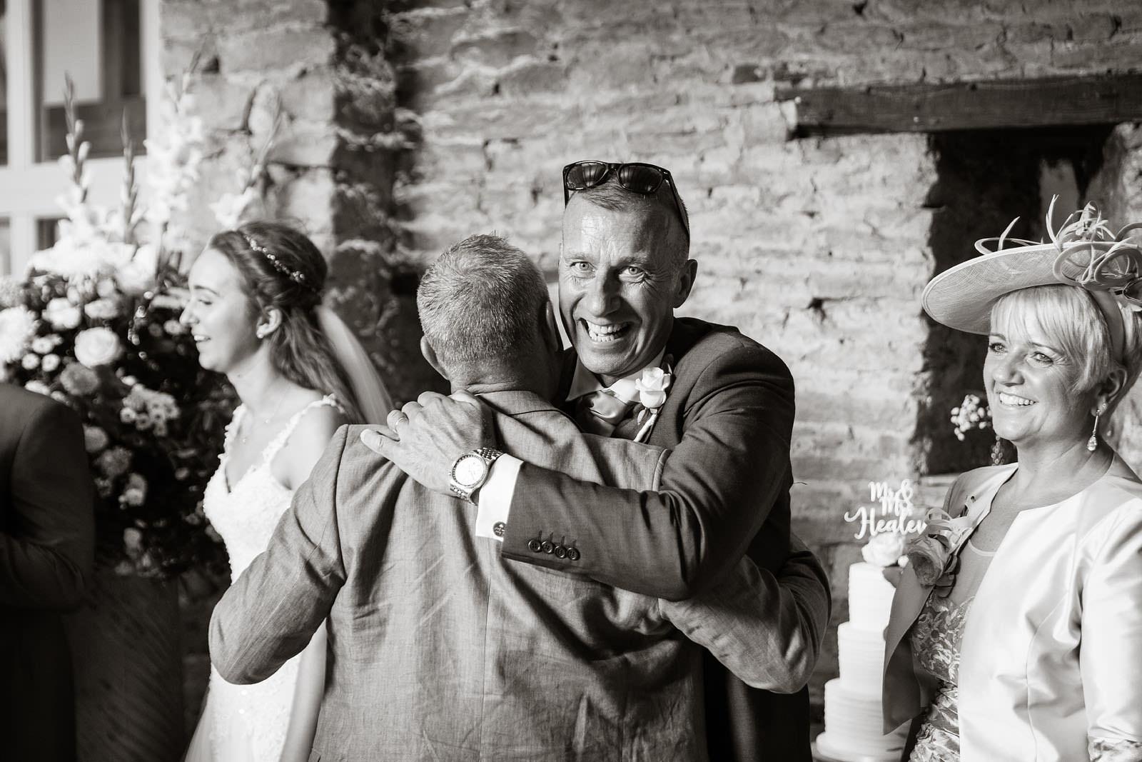 brides dad hugging a guest